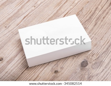 White cardboard box on a wooden background. - stock photo