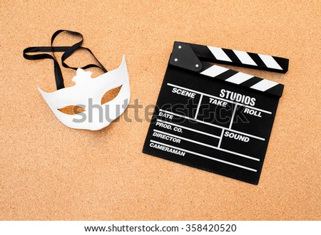 White carnival mask and movie clapper board on cork wooden background - stock photo