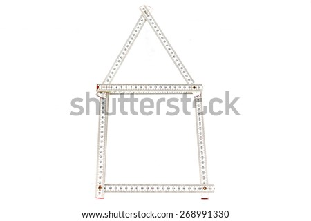 White carpenter rule creating the silhouette of a house on the white background - stock photo