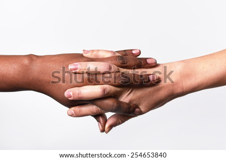 white Caucasian female hands and black African American holding fingers together in world unity and racial love and understanding in tolerance and races diversity cooperation concept isolated close up - stock photo