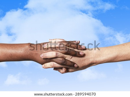 white Caucasian female hands and black African American holding fingers together world unity and racial love and understanding in tolerance and races diversity cooperation concept blue sky background - stock photo