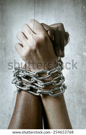 white Caucasian hand chained with iron chain and locked together with black ethnicity female around wrists in togetherness, multiracial respect and understanding concept isolated on grunge background - stock photo