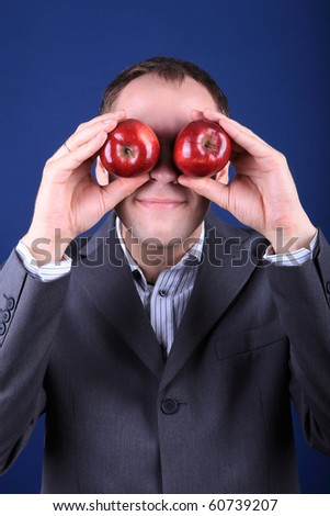 white Caucasian male on dark blue background studio shots holding apples in hands in front of eyes