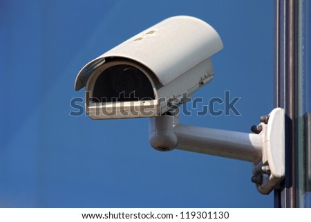 white cctv security camera on blue background