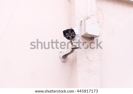 White CCTV security camera on wall.