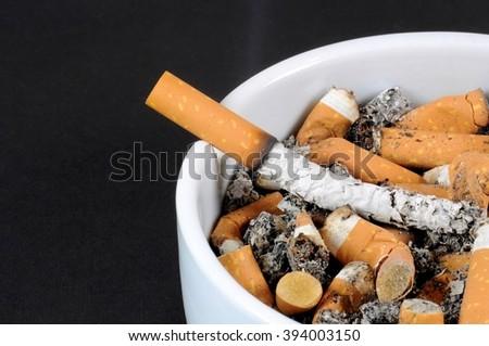 White ceramic ashtray detail full of smokes cigarettes - stock photo