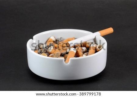 White ceramic ashtray full of smokes cigarettes - stock photo