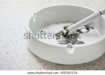 White ceramic ashtray with cigarette - stock photo