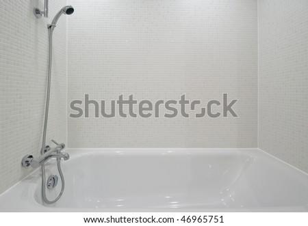 white ceramic bath tub detail with mosaic tiles - stock photo