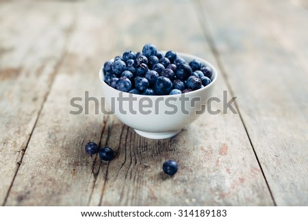 White ceramic bowl filled with sweet blueberries just picked from the plant. The bowl is placed on a wooden table sun-worn and weathered, vintage look