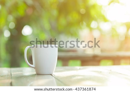 white ceramic coffee cup with soft light effect and blur garden background