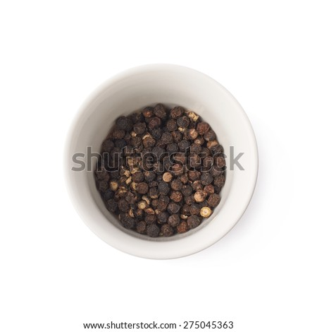 White ceramic cup filled with the black peppercorn, composition isolated over the white background