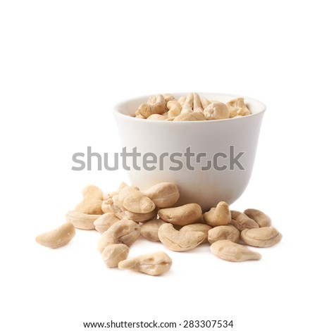 White ceramic cup filled with the cashew nuts spilled around, composition isolated over the white background - stock photo
