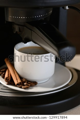 White ceramic cup of fresh coffee with foam in the coffee machine