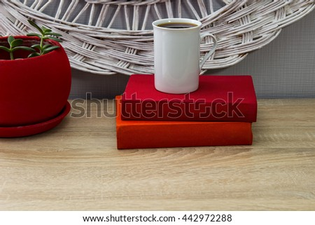 White ceramic cup of tea and an  open books on a wooden table. A red pot with green tree in the background. Reading, learning - stock photo