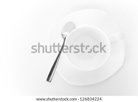 White ceramic cup on saucer with metal spoon above white background. Top view - stock photo