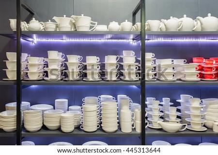 White ceramic dinnerwares on restaurant shelves lighten with LED light. - stock photo