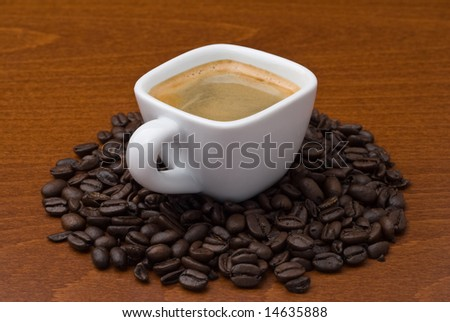 White ceramic espresso cup with spilled coffee beans on wood table - stock photo