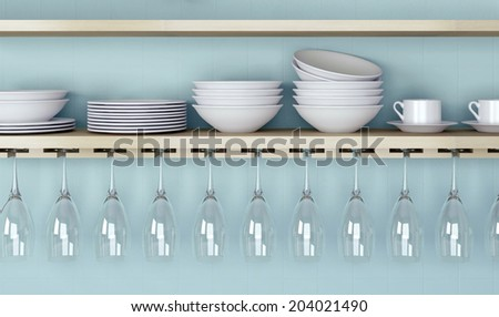 White ceramic kitchenware and wineglasses on the wooden shelf in front of blue wall.  - stock photo