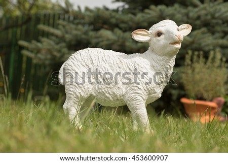 White ceramic plaster statuette of a lamb, sheep on the grass.