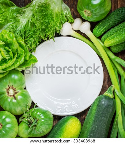 White ceramic plate surrounded by a variety of green vegetables and salads. View from above. selective Focus - stock photo