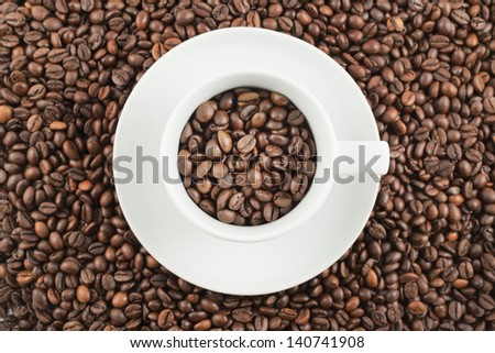 White ceramic plate with cup full of roasted coffee beans as a background composition, top view