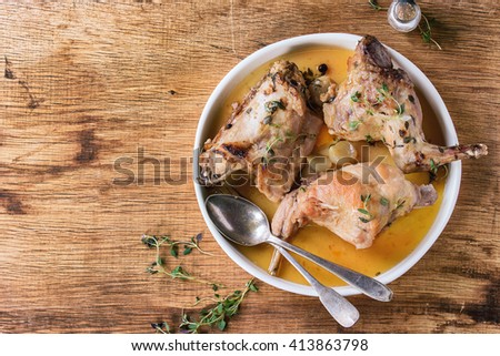 White ceramic plate with stewed rabbit with bouillon, salt and herbs, served with vintage cutlery over wooden background. Flat lay with copy space - stock photo