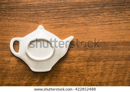 white ceramic teapot sign lie on wooden table from natural material. tea time. - stock photo
