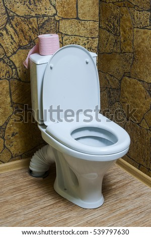 White ceramic toilet in a toilet room with a stone finish