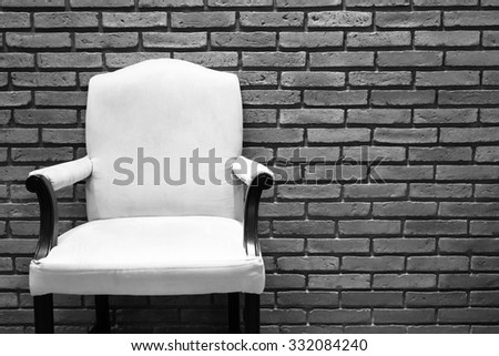 White chair in front of grey and white brick wall. - stock photo