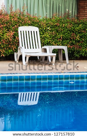 White chair on the poolside of a resort