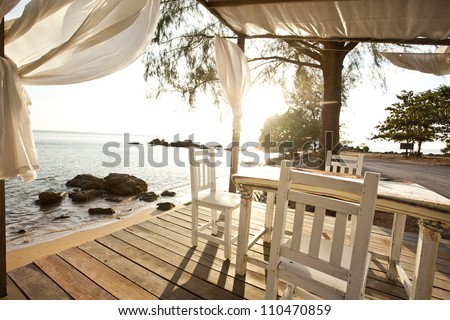 White chairs and table on a balcony with nice view to the sea