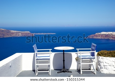 white chairs and tables beside Aegean sea, Santorini, Greece - stock photo