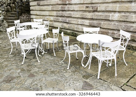 White chairs and tables, detail of a terrace outdoors
