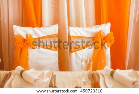 White chairs decorated with orange cloth and crystals