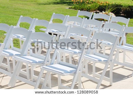 White chairs in rows, ready for the outside wedding guests - stock photo