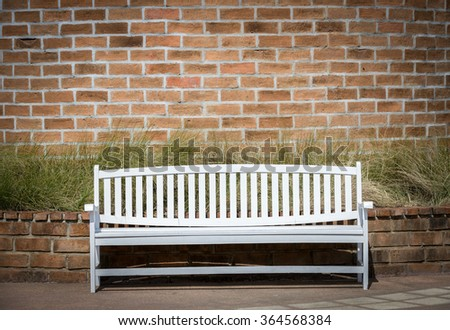 white chairs set up in front of old brick wall