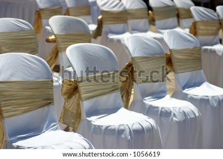 White chairs with gold ribbon at a beach wedding - stock photo