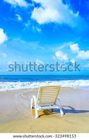 White chaise lounge on the beach of the Caribbean sea wave
