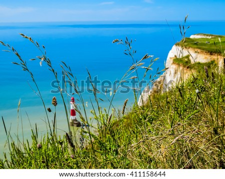 White chalk cliffs and Beachy Head Lighthouse as blurred background. Eastbourne, East Sussex, England. Selective focus - stock photo