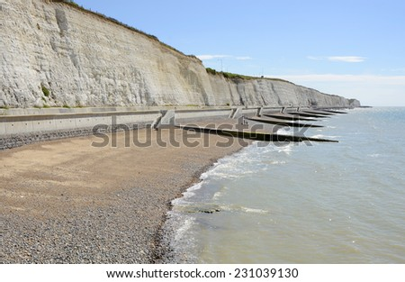 White chalk cliffs and shingle beach on coast at Brighton in East Sussex. England. - stock photo