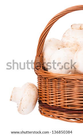 White champignons in a half of wicker basket over white background - stock photo