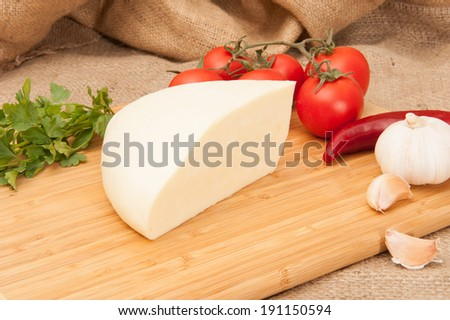 white cheese on wooden board with vegetables and spices