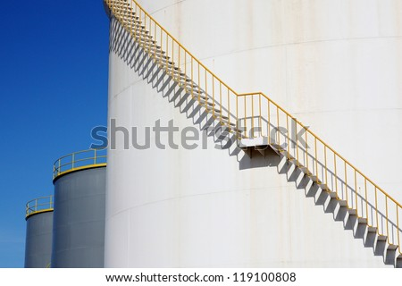 White chemical storage tank with spiral stairs. - stock photo