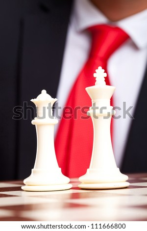 White chess king and queen in front of business man in suit - stock photo