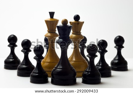 White chess king and queen with the few black pawns and black queen on a white background