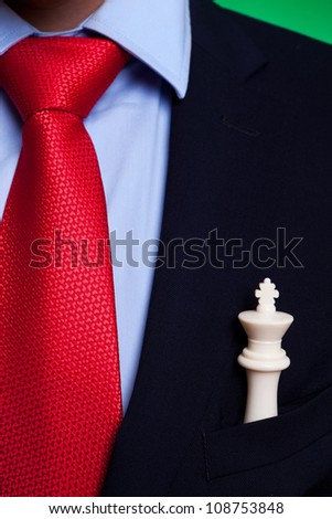 white chess king in the pocket of a business man, closeup picture - stock photo