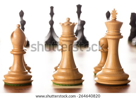 White chess pieces standing on a chessboard with black pieces in the background - stock photo