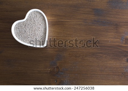 White Chia seeds in heart shaped container on table with copy space - stock photo