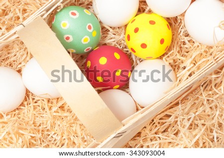 White chicken eggs and hand painted Easter eggs in basket with wood wool; Easter market - stock photo